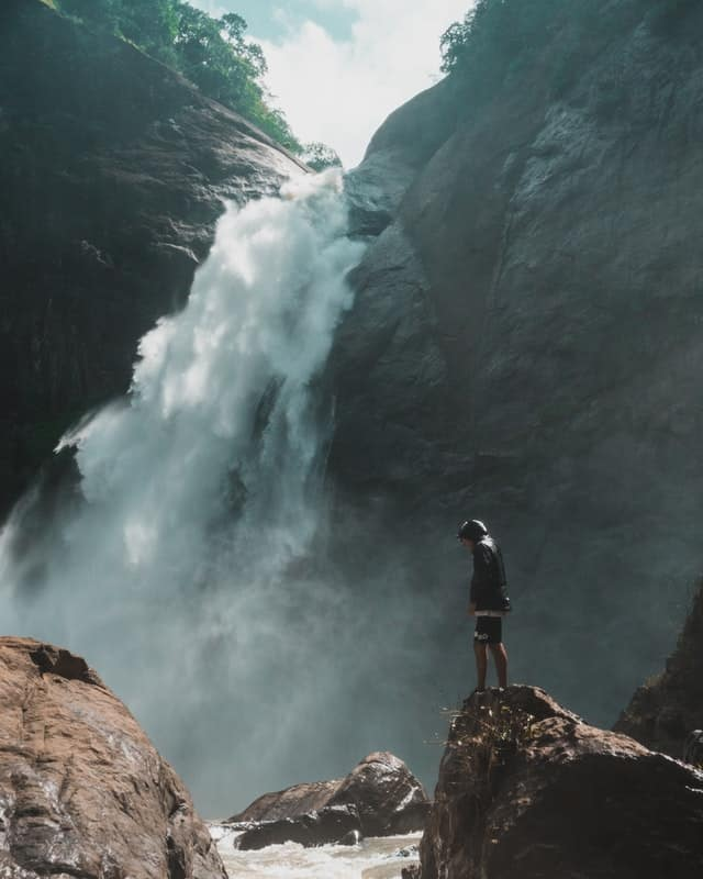 man-standing-on-brown-rock-cliff-in-front-of-waterfalls
