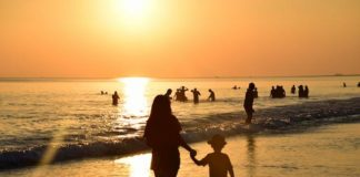 mother-holding-hand-of-baby-sunset-sea