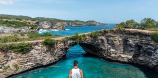photo-of-man-standing-on-cliff-near-lagoon
